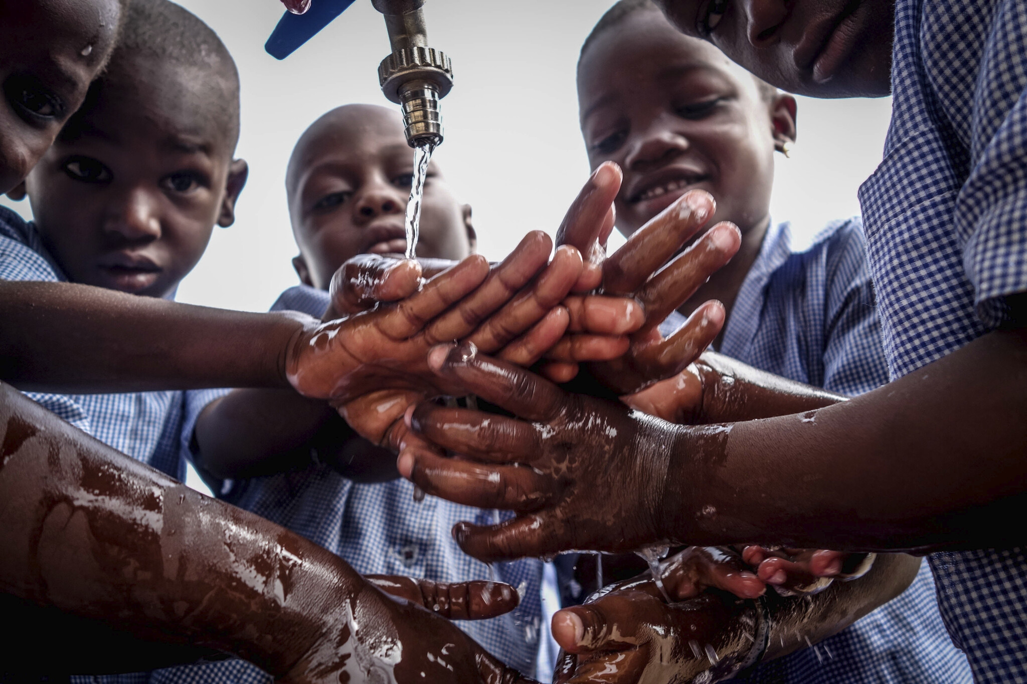 Boys washing hands under outdoor faucet, Jake Meyers, Peace Corps Benin